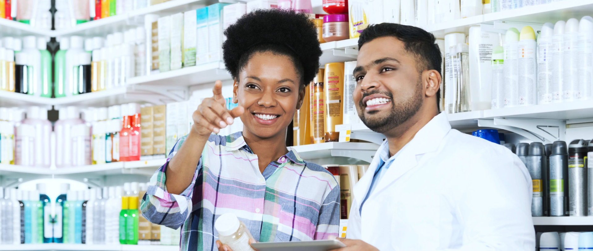 customer pointing at a pharmacy product requiring assistance with a pharmacist